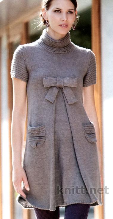 Вязаное платье с коротким рукавом и бантом на груди т выполнено спицами из пряжи средней толщины,  Изящность модели подчеркивается складкой спереди и бантом на груди.